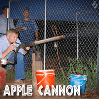 Image of a visitor to Jaemor Farms shooting an apple out of an air compression cannon